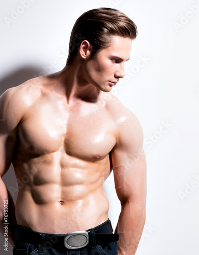 canvas print picture Handsome muscular young man looking sideways.