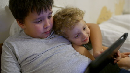Two boys in bed with touch pad. One playing game, another