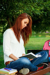 beautiful girl sitting on a bench in the park with a book