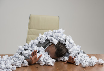 Business woman covered in crumpled papers