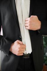 groom straightens his jacket