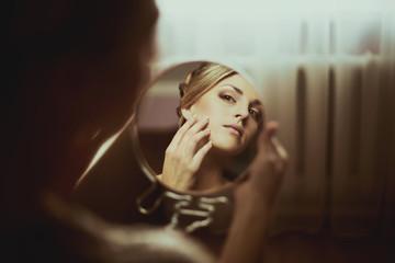 gentle bride looks in the mirror
