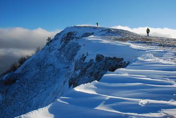 Восхождение на горную вершину солнечным зимним днем