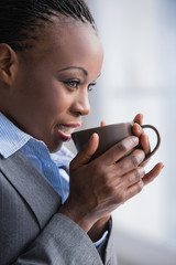 African business woman with mug in hands relaxing