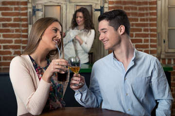 Smiling couple on a date at a bar.