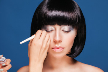 Portrait of a woman making up eyes. on blue background