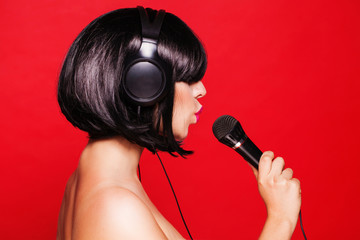 Woman listening to music on headphones enjoying a singing