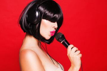 Woman with microphone listening to music on headphones enjoying