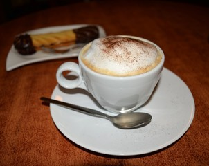 Delicious foamy cappuccino on the wooden table