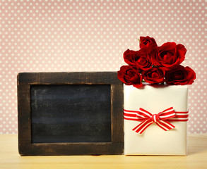 Present box with roses and blank chalkboard