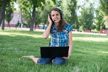 Cute woman in earphones with white laptop in the park