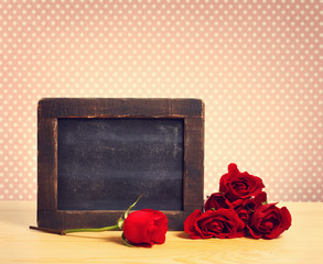 Empty rustic chalkboard with roses