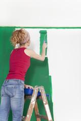 Frau auf Leiter streicht Wand gruen