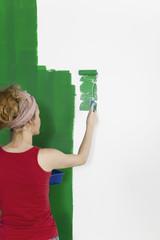 Frau streicht Wand gruen