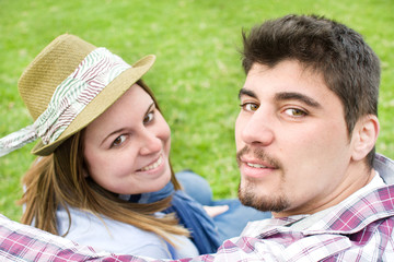 Young man and young woman smiling in park