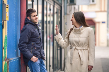 Young man and woman flirting on the street