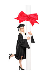 Female graduate student posing with a huge diploma