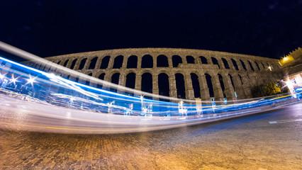 A bus drives through the shot of the famous Segovia Aqueduct.