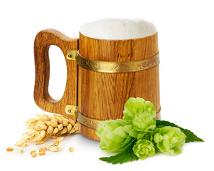 wooden mug with beer, green hops and wheat