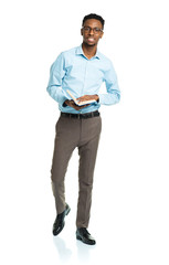 Happy african american college student standing with book on whi