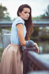 Young beautiful, elegantly dressed woman in the park or outdoor