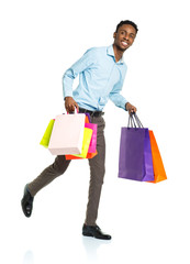 Happy african american man holding shopping bags on white backgr