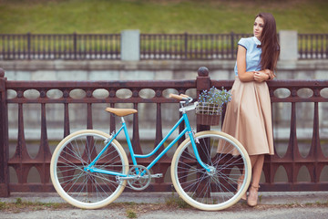 Young beautiful, elegantly dressed woman with bicycle in the par