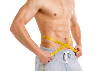 Athletic man with measuring tape on the white