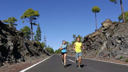 Sport fitness couple running and jogging on road