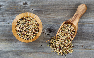 Whole grain rice in wooden kitchenware on rustic wood