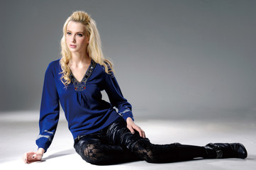 young fashion blond model in blue dress sitting posing