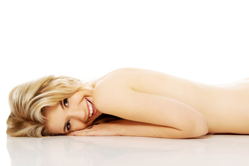 Nude woman lying on belly and looking up