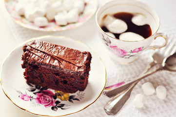 Chocolate cake on a plate and a cup of coffee with marshmellows