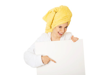 Woman in bathrobe holding empty banner