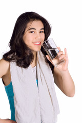 Beautiful biracial teenage girl drinking water while exercising