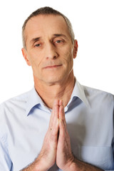 Mature man praying to God