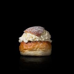 A delicate swedish cream bun on black background.