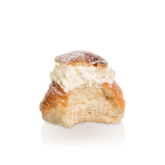 Partly eaten cream bun with only cream filling.