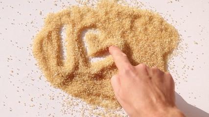 finger paint I LOVE U on brown sugar surface