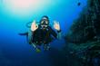 Young woman scuba diving signals okay - 76783541