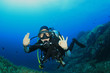 Young woman scuba diving signals okay - 76783964