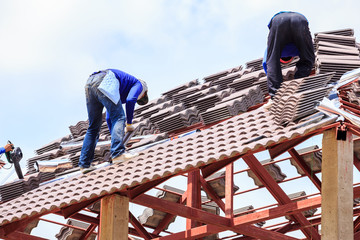 Worker install roof tile for new house