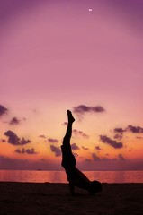 Silhouette of body man acts yoga on the sand beach with sunset