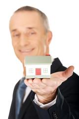 Businessman holding house model