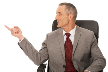 Businessman sitting on armchair and pointing left