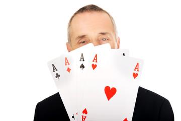 Portrait of elegant man with four aces
