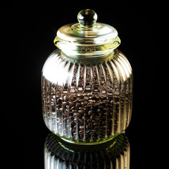 Glass vintage jar full of coffee beans on black background