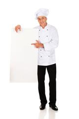 Chef in white uniform holding empty banner