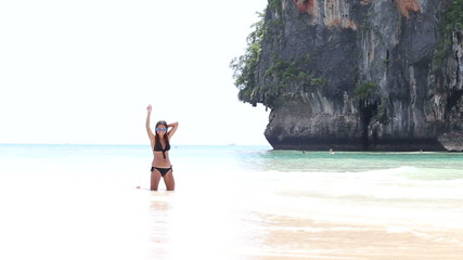 girl in a bathing suit and sunglasses raise her hand and enjoy s