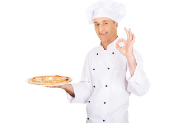 Chef baker with italian pizza showing perfect sign